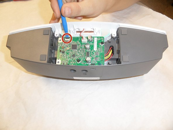 After removing the bottom plate, you will have visibility of the logic board. Using a plastic opening tool, lift the small black latch holding the ribbon cable. Slide the ribbon cable loose from the logic board.