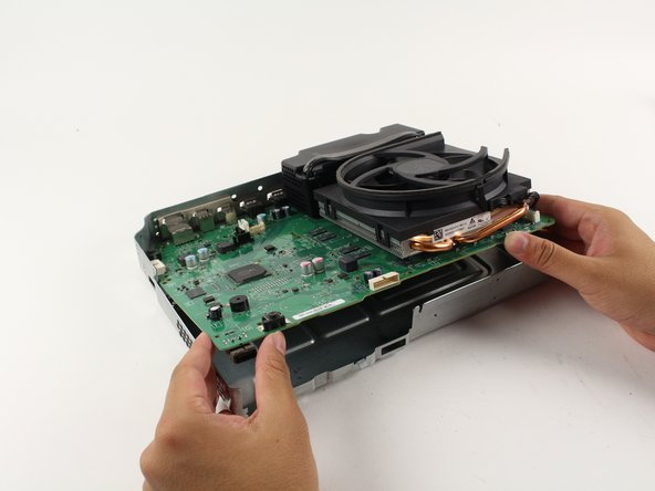 Now that the clamp is removed, gently lift the motherboard from its edges out from the metal casing. The motherboard should come out with ease.