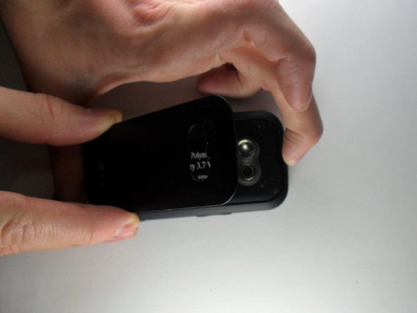 With one hand, push the rectangular button located on the back top-side of the phone.