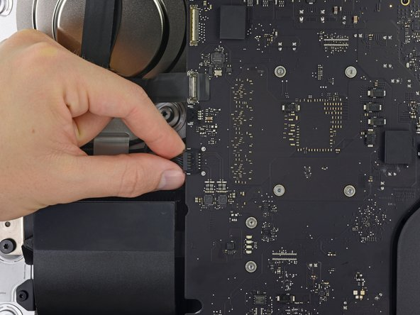 Gently pull the left speaker cable straight out of its socket on the logic board.
