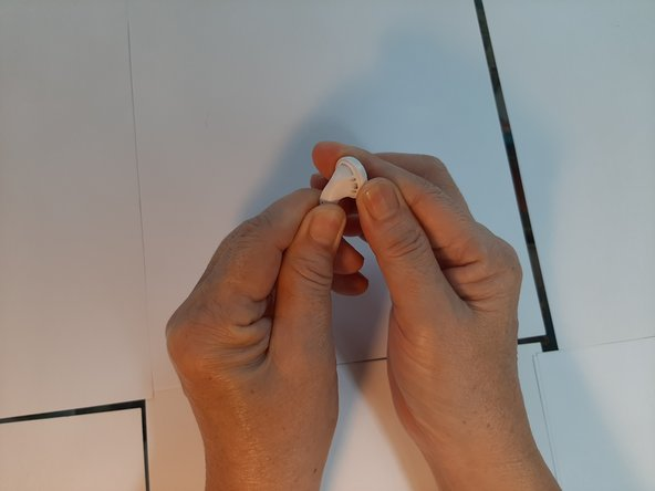 Hold firmly onto the earbud stem with one hand, and pinch the sound driver with the other hand. Gently but firmly apply a prying motion to separate the body from the sound driver.