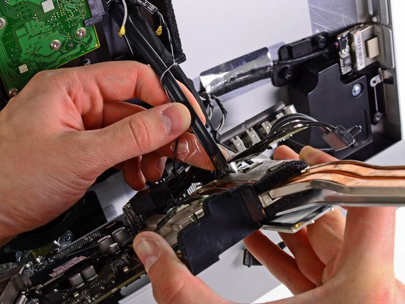 If present, peel off the tape securing the hard drive SATA cable to the logic board.
