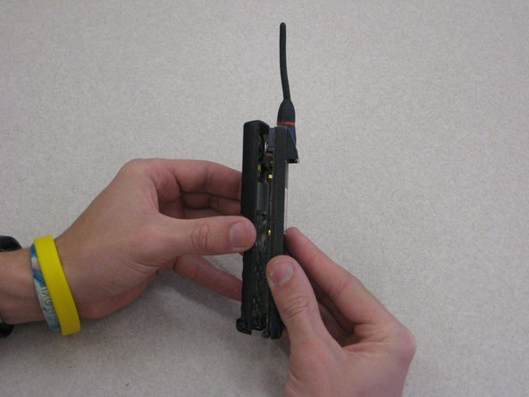 Grab opposite panels of the phone casing and carefully open and pull apart the phone, as shown in the image.