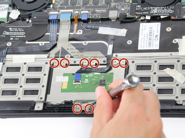 """Using a Phillips #00 screwdriver, remove the eight 1/8"""" screws surrounding the trackpad."""
