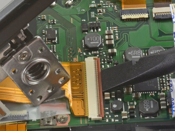 To remove the ribbon cable, flip back the orange lock on the large ZIF connector with the flat end of a spudger.