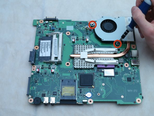 Flip the motherboard over. Using a Phillips #1 screwdriver, remove the two 3-mm screws from the fan.