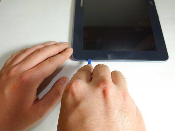 Insérez un outil de levier en plastique ou un médiator entre le verre et le boîtier en plastique.