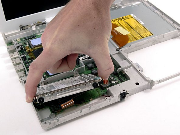 Lift the hard drive up, carefully guiding the cable through the slot in the lower case.