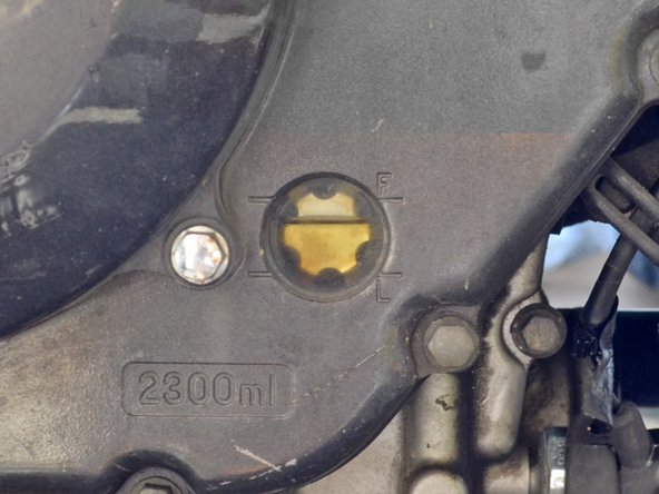 Tilt the motorcycle up off of its kickstand until it is vertical so that you can check the oil level through the sighting glass.