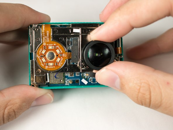 Remove the motherboard from from the back case by gently pulling on the lens housing.