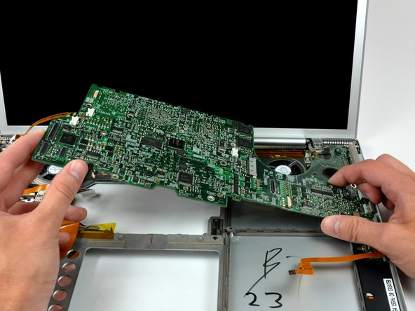 Lift the logic board from its left edge and rotate it toward the right side of the lower case.