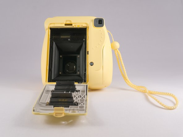 Open the rear compartment and remove the film cartridge.