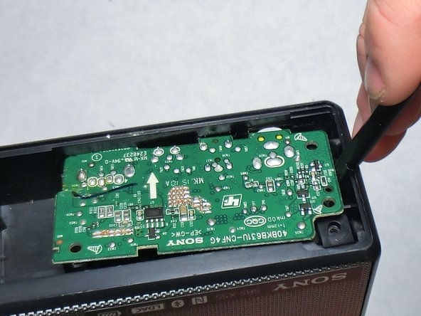 Remove the I/O board from the rest of the speaker. A plastic spudger can aid in this process if it is inserted into the edge as shown and gently pried.