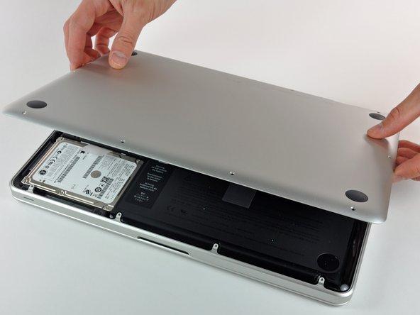 Hebe die Unterseite vorsichtig an und drücke sie Richtung Rückseite des Laptops, um die Halterungsclips zu lösen.