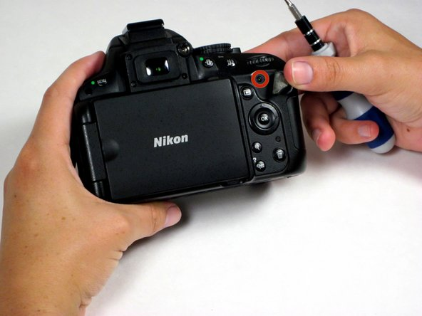 Using a fingernail, gently peel back the black rubber thumb grip, which is attached to the chassis with a strong adhesive, and remove the concealed screw underneath it.