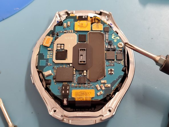 Remove one J00 phillips-head screw from the mainboard, freeing the board from the frame. The board still has 5 connectors and adhesive, do not begin the removal of the board.