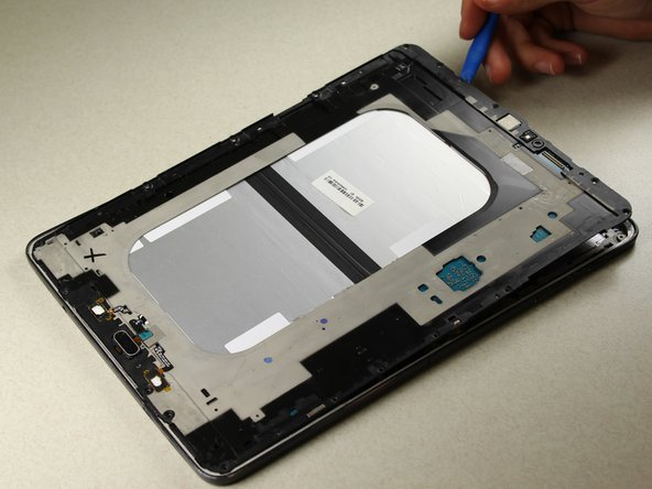 Use the plastic opening tools to gently separate the middle panel from the rest of the device.