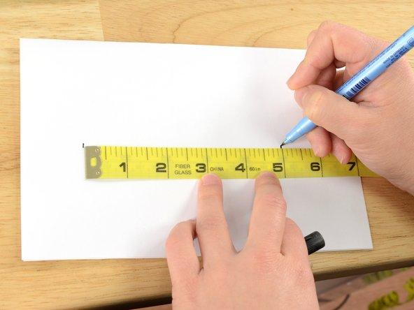 Su un pezzo di carta, segnare gli estremi della lunghezza dello strappo, aggiungendo 2,5 cm.