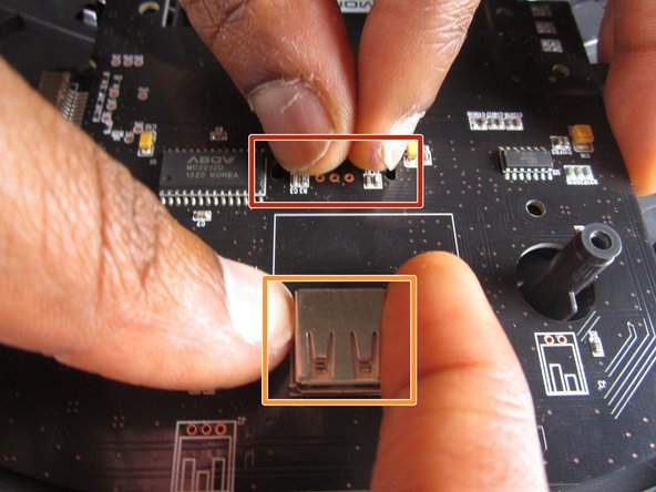 Pinch the two tabs together, shown here, to loosen the motherboard out of the vacuum.