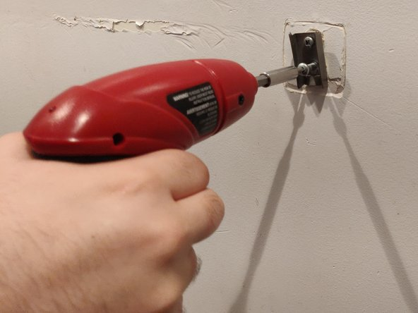 After unscrewing the holder, take it off and begin unscrewing the screws in the wall. The type of screwdriver depends on the screws used.