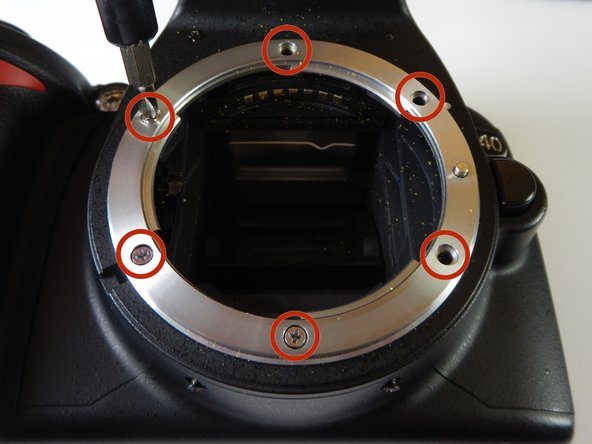 Remove the six 5.0 mm Philips #0 screws that go through the lens mount.