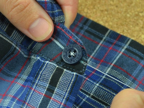 Drive the needle back up through the underside of the fabric and into the first hole that you threaded.