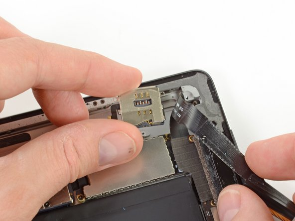 Holding the headphone jack assembly cable out of the way, remove the SIM board from the iPad.