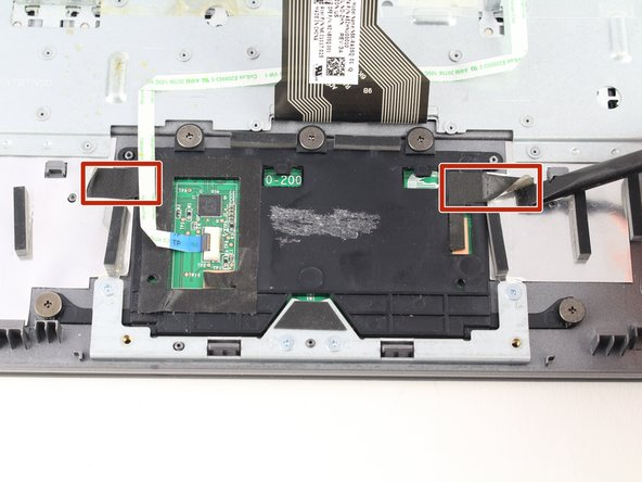 Lift up the tape on either side of the trackpad.