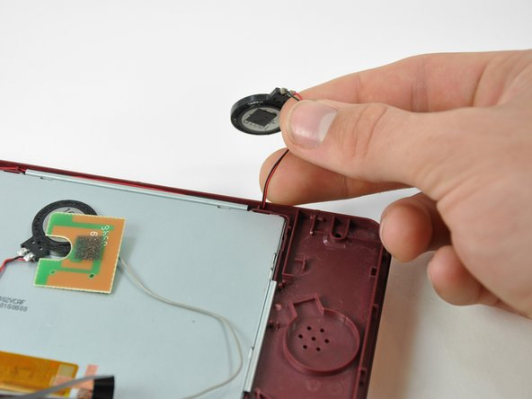De-route the left speaker cable along the top edge of the upper LCD.