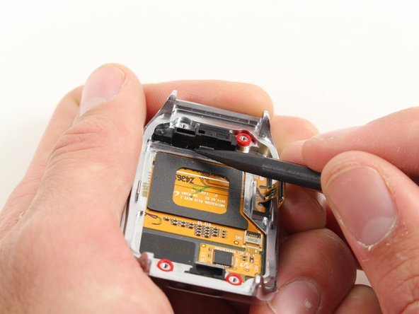 Insert the spudger into the small opening underneath the black home button assembly and pry it off the casing.