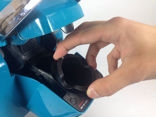 Firmly rock the K-cup holder from side to side, loosening the K-cup holder from its seat.