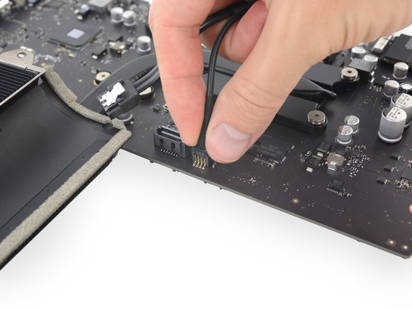 Fasse den Versorgungsstecker der Festplatte an und ziehe ihn vorsichtig aus seinem Anschluss auf dem Logic Board.