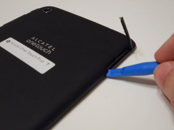Begin working by using the plastic opening tool to remove the back cover of your Alcatel One Touch Pop 7. Opening the flap as shown in the picture will give you an easier start.