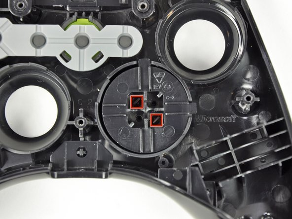 The D-pad is secured to its backing by two diagonal clips, shown in red.