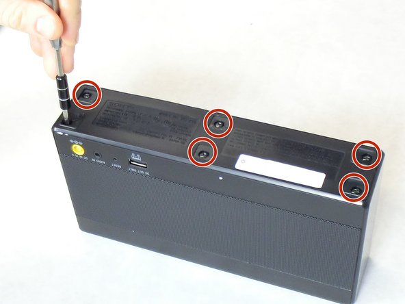 Locate the six 9 mm screws on the bottom of the SRS-X55 and remove them using a Phillips head #2 screwdriver.