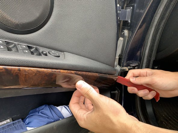 Using a plastic pry tool, carefully pry off the mock wood trim.