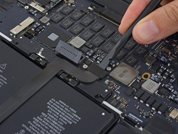スパッジャーの平面側先端を使って、基板中のソケットからtouchpadケーブルコネクターの接続を外します。