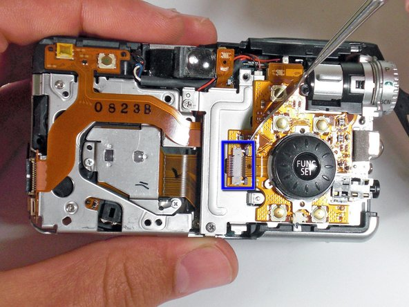 Gently pry up the tab with a metal spudger and remove the ribbon cable.