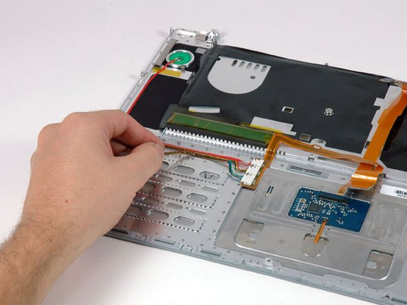 Peel up the Bluetooth data cable from the adhesive on the upper case.