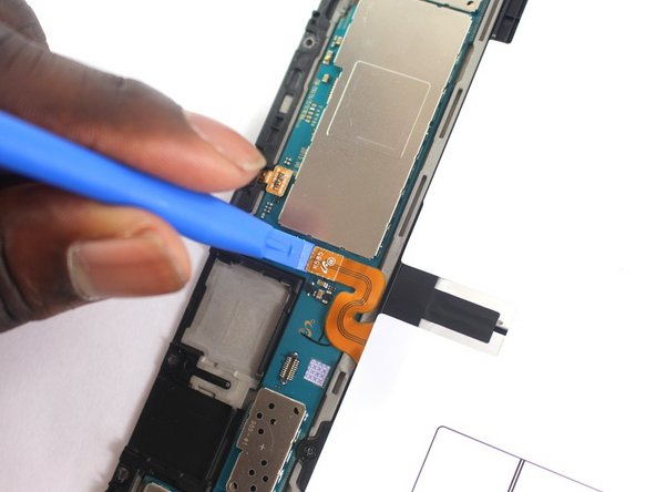 Using the plastic opening tool, detach the orange ribbon cable connecting the battery to the motherboard.