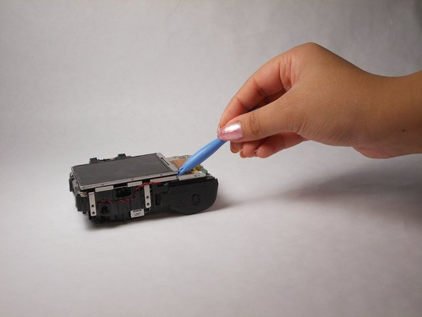 Using a prying tool, carefully lift up the LCD screen but do NOT pull it off.
