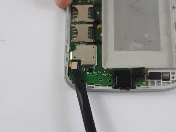Using a spudger, remove the two metal pieces connecting the  motherboard to the front casing.