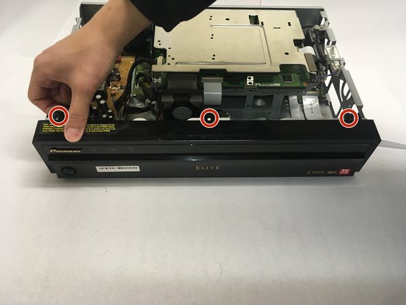 Unlatch the three plastic connectors on the top of the receiver that hold the front panel to the device casing.