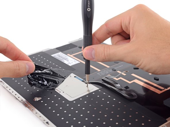 The trackpad is trapped under tape and a metal shield, but it's nothing we haven't handled before.