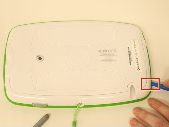 Using a plastic opening tool, pry off the plastic border by inserting it in the space between the green bumper and the white plastic on the edge of the tablet.