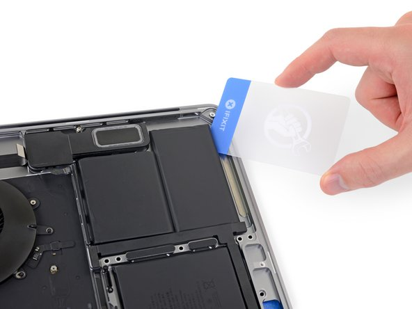 After a couple minutes, insert one corner of a plastic card underneath the battery, starting from the lower edge of the bottom, right-most cell.
