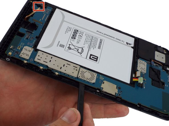 Lift the motherboard free from the power and volume button side.