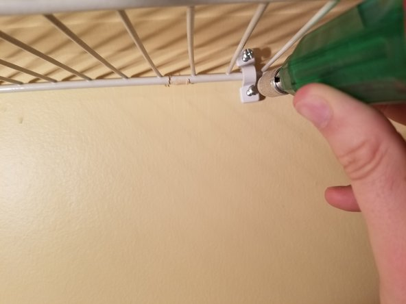Use a Phillips screw driver to screw the c-clamps into the plastic anchors and reinforce the rack.