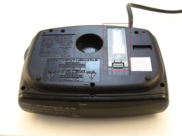 Find the battery compartment on the bottom of the clock radio.