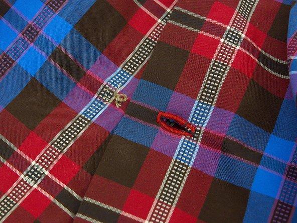 How do I sew a button onto my Vaude shirt?